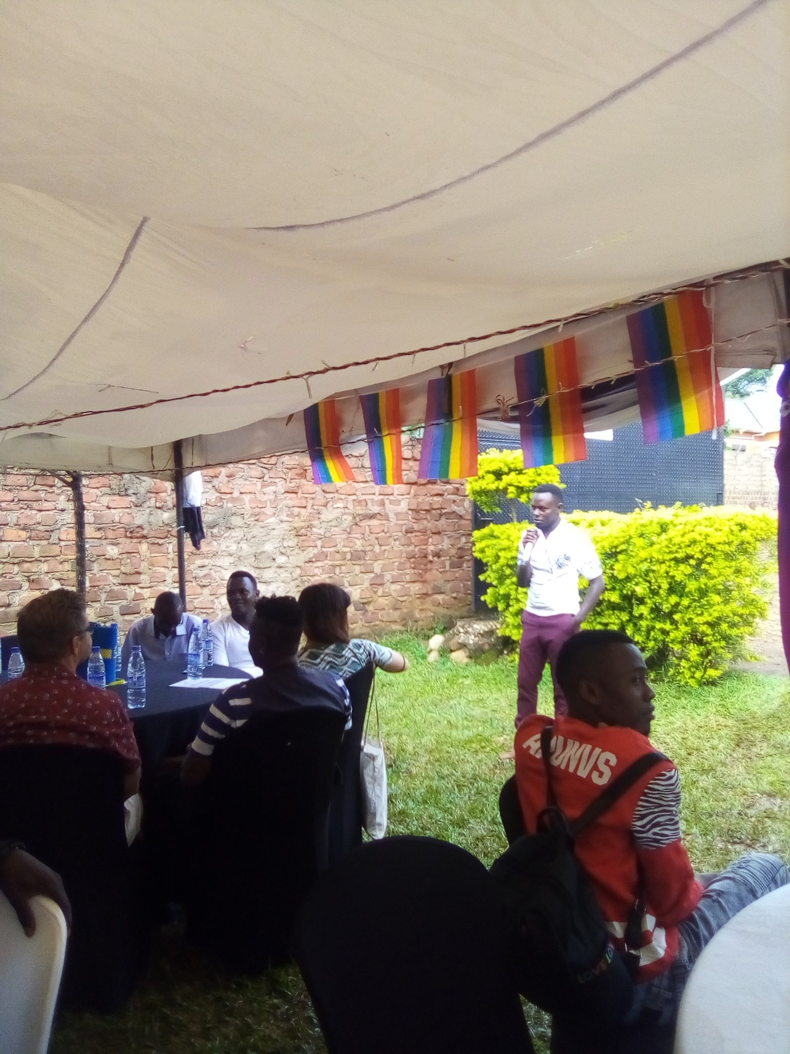 One person is standing and speaking into a microphone outside of a white tent with rainbow flags hanging down. People are seated at tables, listening.